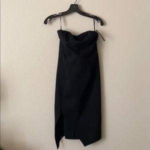 Black body-con cocktail dress with a leg slit.